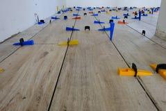 Installation des tuiles de style du bois de porcelaine sur un plancher photographie stock