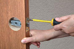 Installation of the door lock, a locksmith hand close-up. Installing the door handle with a latch in the interior doors, close-up hands of the installer with a Royalty Free Stock Image