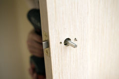 Installation of door lock. Using a screwdriver to. Carpenter at lock installation with electric drill into wood door Royalty Free Stock Photography