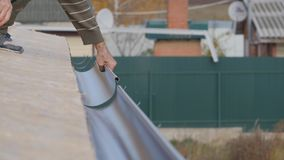 Installation of drainage system of a private house. The laying of gutters on the hooks.