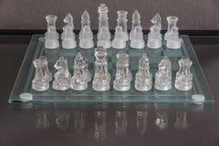 Installation du début du jeu d'échecs sur un échiquier en verre Images stock