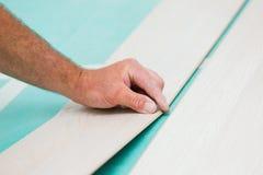 Installation du plancher en stratifié avec la texture en bois photo libre de droits