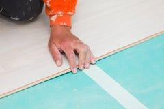 Installation du plancher en stratifié avec la texture en bois image stock