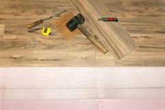Installation du plancher en stratifié en bois avec l'isolation dans la maison, nouveau plancher d'arrangement après inondation Images stock