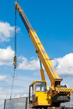 Installation of a fence by a mobile crane. Mobile crane during installation a fence stock images