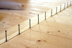 Installation of the floor in a house. Screws lined up before tightening Stock Image