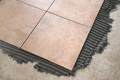 Laying floor tiles. Installation of floor tiles with tile adhesive stock images