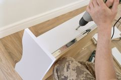 Installation of furniture. Closeup of workers hand with professional tools and furniture details.  royalty free stock photo