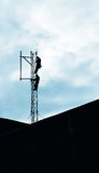Installation of a GSM antenna. This photograph represent an installation of a GSM antenna performed by two workers on a telecommunication tower Royalty Free Stock Photography