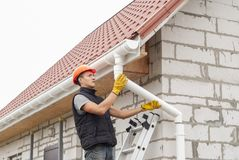 Installation gutter system. Construction worker installs the gutter system on the roof Royalty Free Stock Photography