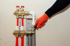 Installation individual of home heating. A plumber attaches the tube to the collector heating. Underfloor heating installation. Close up on water floor heating royalty free stock images