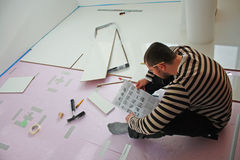 Installation Instructions. Workers laid laminate in home renovation Royalty Free Stock Photos