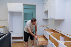 Installation kitchen. Worker installs doors to kitchen cabinet. Stock Photo