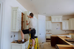 Installation of kitchen. Worker installs doors to kitchen cabinet. Installation of doors on kitchen cabinets stock images