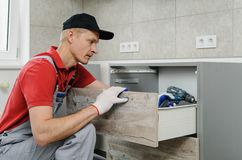 Installation of kitchen. Workman fixes the drawer in cabinet Royalty Free Stock Photo