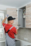 Installation of kitchen. Workman installs doors to kitchen cabinet Stock Photos