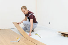 Installation of a laminate floorboard. The worker is attaching one bar after another Stock Image