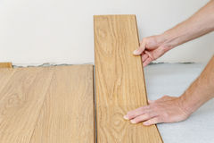 Installation of a laminate floorboard. The worker is attaching one bar after another Stock Photos