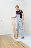 Installation of a laminate floorboard. The worker keeps a laminate floorboard for laying on the floor Stock Image