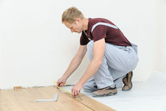 Installation of a laminate floorboard. The worker is measuring the distance to the wall Stock Photos