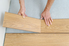 Installation of a laminate floorboard. Worker`s hands are attaching one bar after another Royalty Free Stock Photos