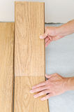 Installation of a laminate floorboard. Worker`s hands are attaching one bar after another Royalty Free Stock Photography