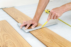 Installation of a laminate floorboard. Worker`s hands are marking the cutting line Royalty Free Stock Photos