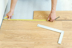 Installation of a laminate floorboard. Worker`s hands are measuring the distance to the wall Royalty Free Stock Photos