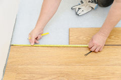 Installation of a laminate floorboard. Worker`s hands are measuring the distance to the wall Stock Photography