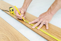 Installation of a laminate floorboard. Worker`s hands are measuring a piece of board to cut into the future Royalty Free Stock Image