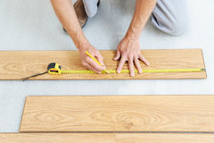 Installation of a laminate floorboard. Worker`s hands are measuring a piece of board to cut into the future Royalty Free Stock Photography