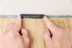 Installation of a laminate floorboard. The worker`s hands are placing a wedges between the wall and the floorboard Royalty Free Stock Photo
