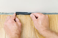 Installation of a laminate floorboard. The worker`s hands are placing a wedges between the wall and the floorboard Stock Image