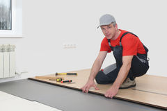Installation of a laminate in the room. Man installing new laminated wooden floor royalty free stock photo