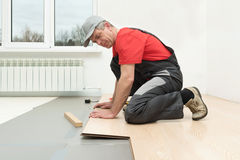 Installation of a laminate in the room. Man installing new laminated wooden floor royalty free stock image
