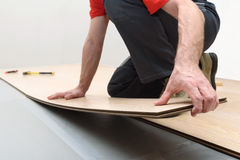 Installation of a laminate in the room. Man installing new laminated wooden floor stock photos