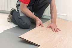 Installation of a laminate in the room. Man installing new laminated wooden floor stock photo