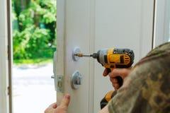 Installation locked interior door knobs, close-up woodworker hands install lock. Stock Photo