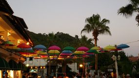 Installation made of hanging umbrellas. Composition made of red orange yellow blue pink green and colorful hanging umbrellas in crowd place near building and Royalty Free Stock Photography