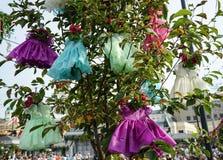 Installation med hängande barns klänningar på trädet arkivfoton