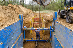 Installation of metal supports to protect the walls of the trench. stock images