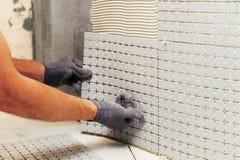 Installation of mosaic tiles. Stock Photos
