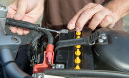 Installation of the motorbike battery Royalty Free Stock Photos