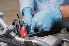 Installation of the motorbike battery Stock Photos