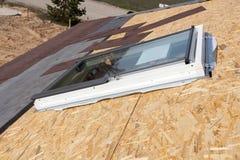Installation of new plastic mansard or skylight  window  on a asphalt shingle roof. Stock Images