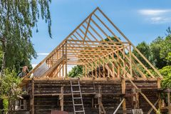 Installation of a new wooden roof on a dwelling house by a team of joiners and roofers. Installing a new wooden roof in a dwelling house by a team of joiners and stock photography