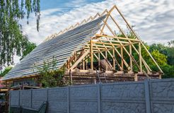 Installation of a new wooden roof on a dwelling house by a team of joiners and roofers. Installing a new wooden roof in a dwelling house by a team of joiners and stock photo