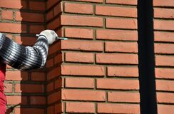 Free Installation Of Fired Brick Cladding. After Gluing To The Wall, The Joints Are Filled With Cement. The Worker Strokes With The Hel Stock Photography - 216213692
