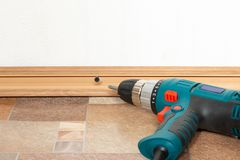 Installation of plastic floor plinth. Interior details. Installation of plastic floor plinth heavy screwdriver lying next to the on the wooden floor royalty free stock image