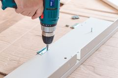 Installation of plastic floor plinth. Interior details. Close up electric drill and nails left on wooden floor. Installation of plastic floor plinth royalty free stock images